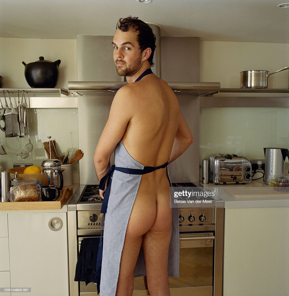 Naked man wearing apron in kitchen, looking over shoulder, portrait : Stock Photo
