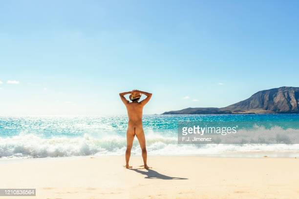 naked man with his back in the beach - naturisme photos et images de collection