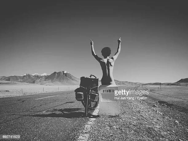 Naked Man With Obscene Gesture Sitting On Sign By Bicycle Amidst Road Against Clear Sky