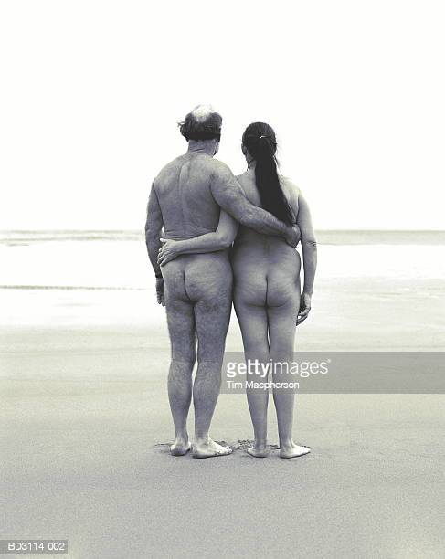 naked mature couple on beach, arms around each other, rear view (b&w) - vieilles fesses photos et images de collection