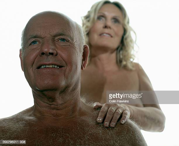 naked mature woman with hand on senior man's shoulder (focus on man) - female hairy chest stock pictures, royalty-free photos & images