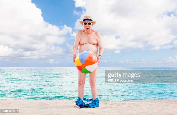 Naked older Caucasian man covering waist with beach ball