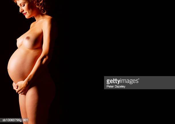 naked pregnant woman looking down at belly, smiling, side view - weibliche brust schwanger stock-fotos und bilder