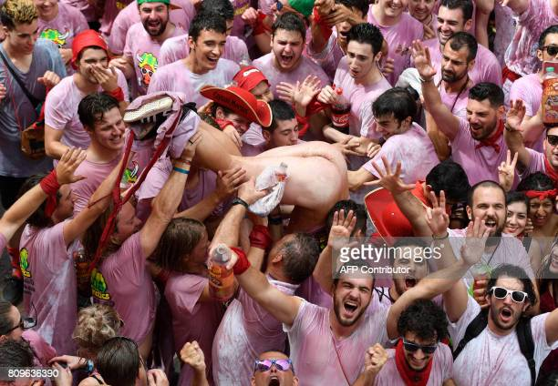 A naked reveller is tossed by other participants as they celebrate the 'Chupinazo' to mark the kickoff at noon sharp of the San Fermin Festival in...
