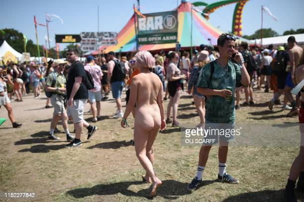 A naked reveller walks through the Glastonbury Festival of Music and Performing Arts on Worthy Farm near the village of Pilton in Somerset South West...