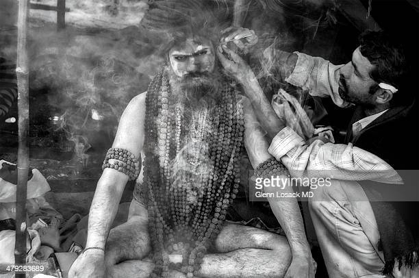 Naked Sadhu having his ears cleansed with a pin point needle, a very common procedure done all over the subcontinent. Kumbh Mela Allahabad 2013