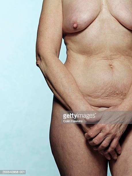 naked senior woman, mid section, front view - senioren aktfotos stock-fotos und bilder
