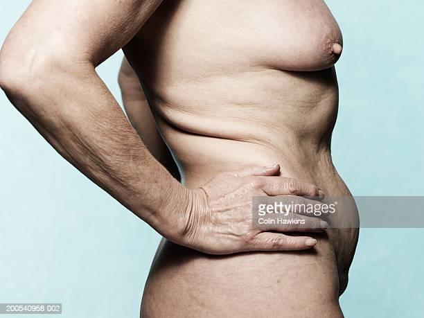 naked senior woman with arms akimbo, mid section, side view - senioren aktfotos stock-fotos und bilder