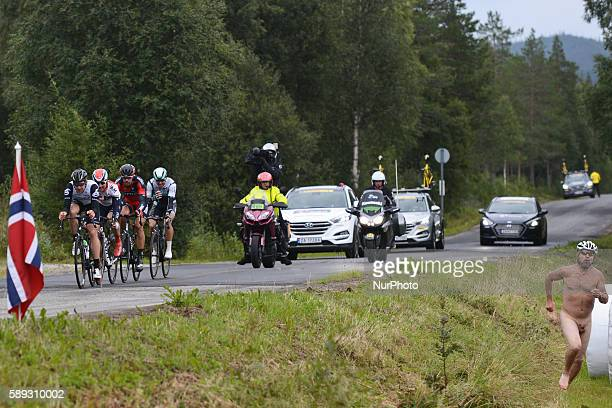 A naked supporter runs with a breakaway of four riders passing by during the third stage 'the queen stage' of the Arctic Race of Norway 2016 the...