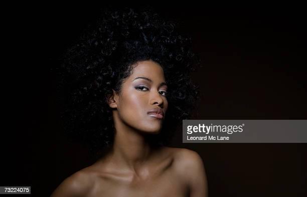 Naked woman against black background, portrait, close-up