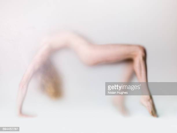 naked woman behind frosted glass backbending