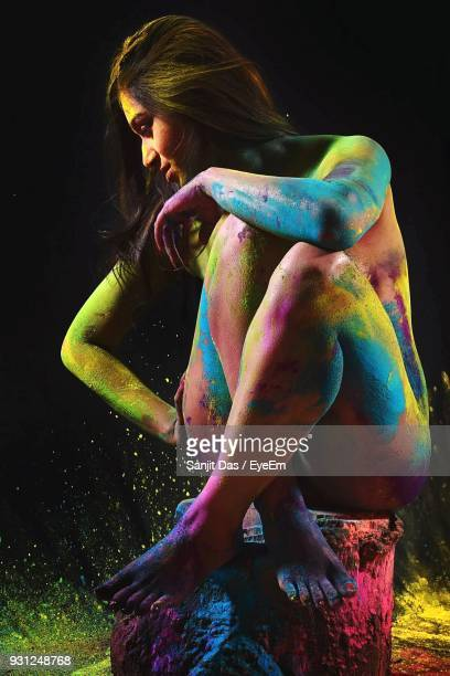 naked woman covered with powder paint against black background - nude hindu women stock photos and pictures