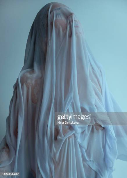 Naked woman covered with wet blue textile looking like sculpture
