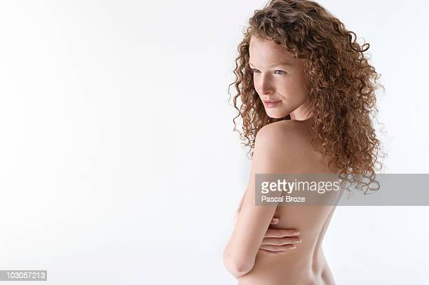 Naked woman hugging herself