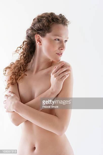 naked woman hugging herself - mani su seno foto e immagini stock
