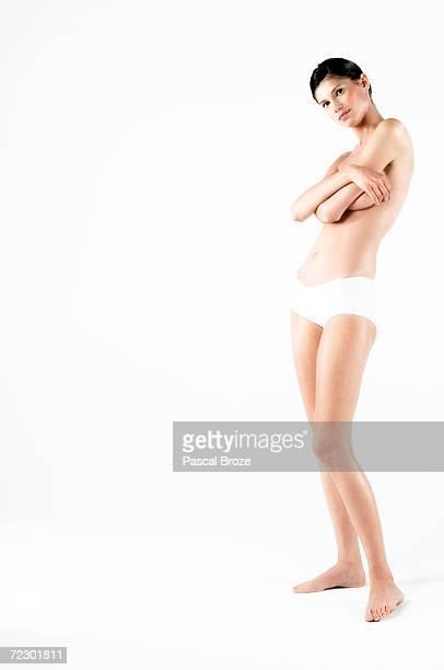Naked woman in panties, hands on her breasts (studio)