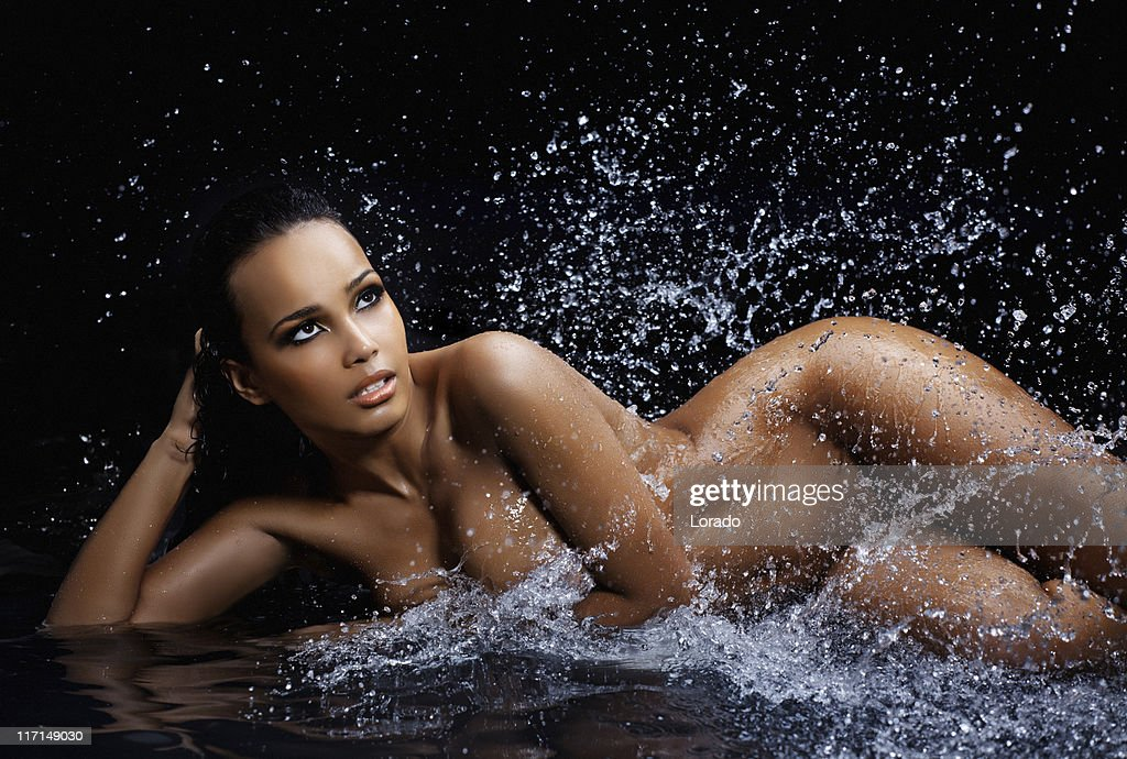 naked woman laying in splashes water : Stock Photo