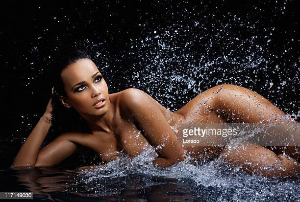 naked woman laying in splashes water