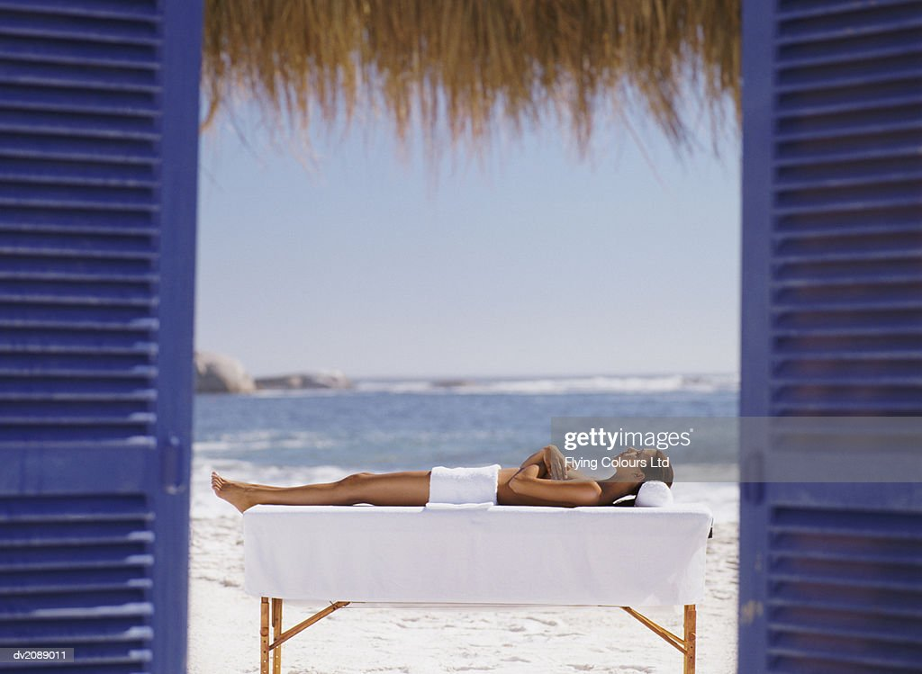 Naked Woman Lies on a Bench on the Beach, Covered With a Towel, Sunbathing : Stock Photo