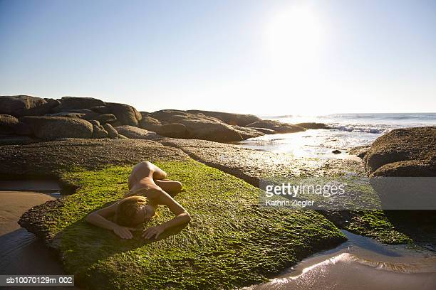 Naked woman lying on rock covered with seaweed
