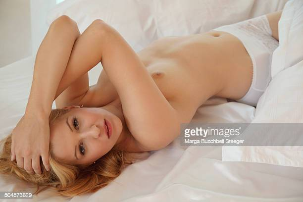 naked woman on bed - dressed undressed women stock pictures, royalty-free photos & images