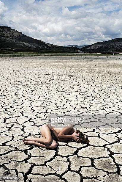 Naked woman on cracked earth