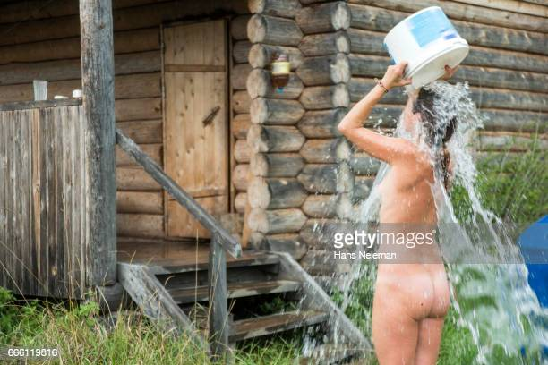 Naked woman pouring water on her body
