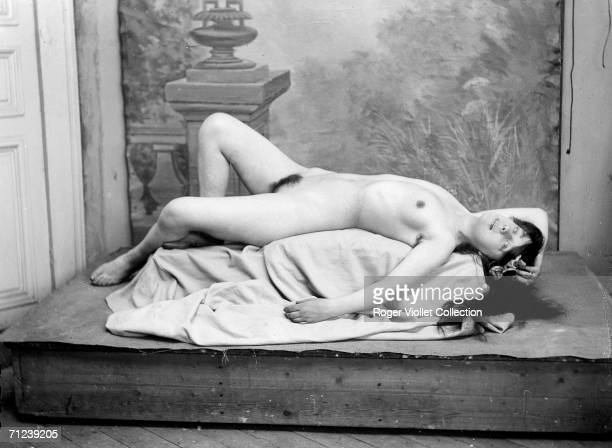 A naked woman reclines on a clothcovered pedastel in front of painting France 1898