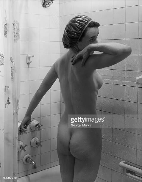 Naked woman showering, rear view