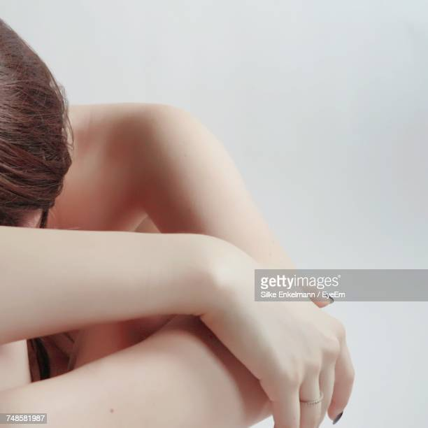 Naked Woman Sitting Against Wall At Home