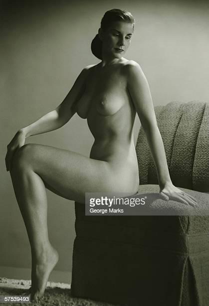 Nua mulher sentada na cadeira no estúdio, (B & W, Retrato