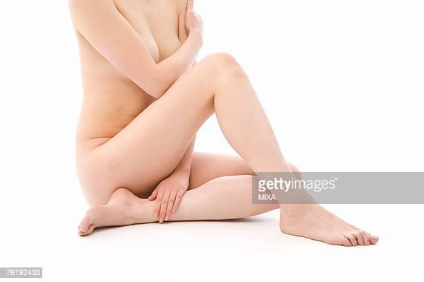 Naked woman sitting on floor