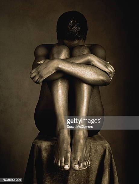 Naked woman sitting on pedestal, knees drawn up to face (B&W)