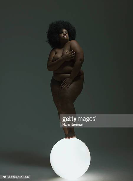 naked woman standing on glowing sphere, looking up - images of fat black women stock photos and pictures