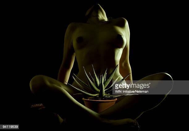 Naked woman with a potted plant
