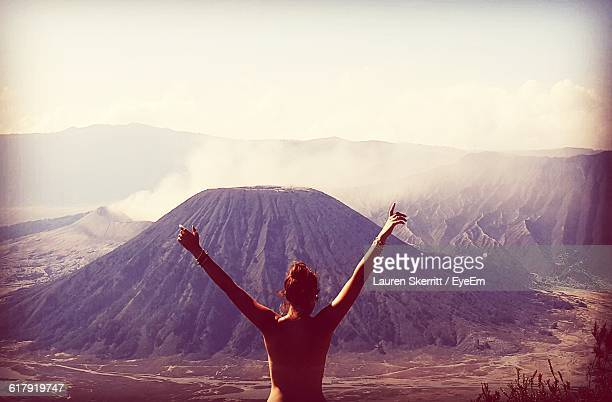 Naked Woman With Arms Raised Standing Against Mountains