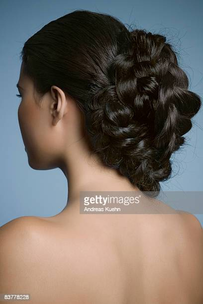 Naked woman with braid, back view.