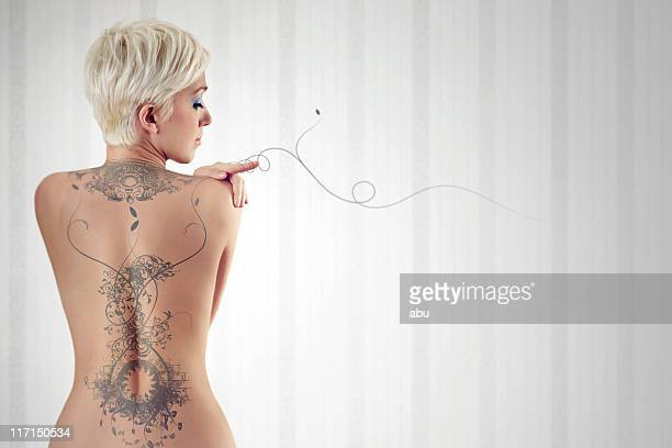 nudo di donna con enorme sul suo tatuaggio sul dietro - donna schiena nuda foto e immagini stock