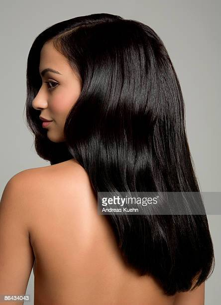 Naked woman with long shiny black hair, back view.