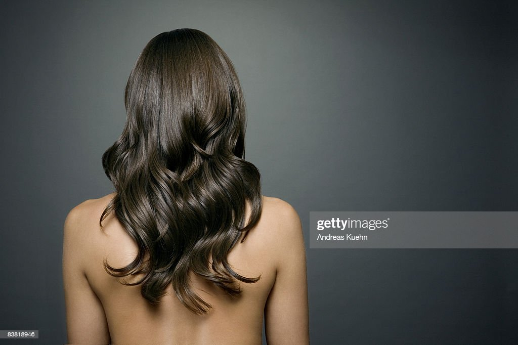 Naked woman with long shiny wavy hair, back view. : Stock Photo