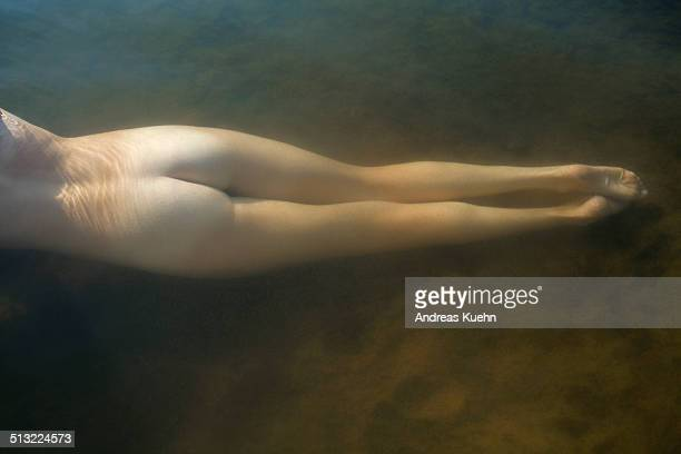 Naked woman's lower body under water in a pond.