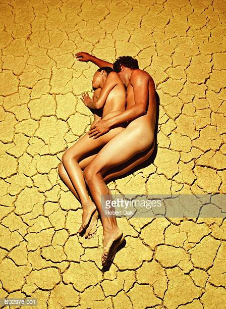 naked young couple lying on cracked mud surface, elevated view - naakte man en profiel stockfoto's en -beelden