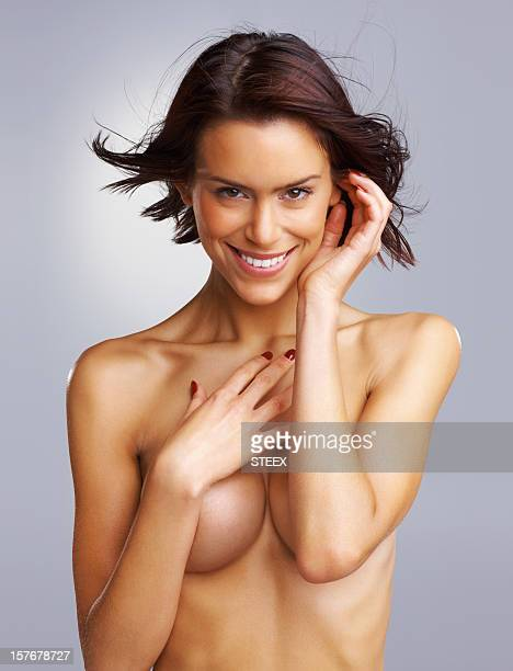 Naked young female covering breast against colored background