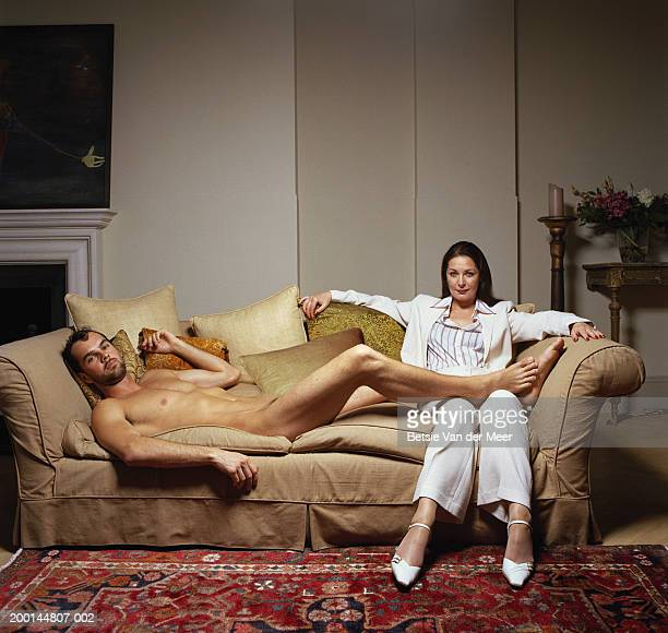 naked young man lying on sofa, feet on mature woman's lap, portrait - cougar woman fotografías e imágenes de stock