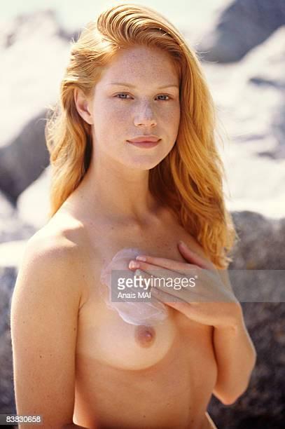 naked young woman applying suncream on her chest, outdoors - pechos de mujer playa fotografías e imágenes de stock