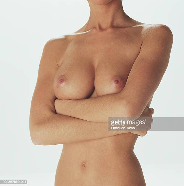 naked young woman, arms crossed, mid section - nackte frau brüste stock-fotos und bilder