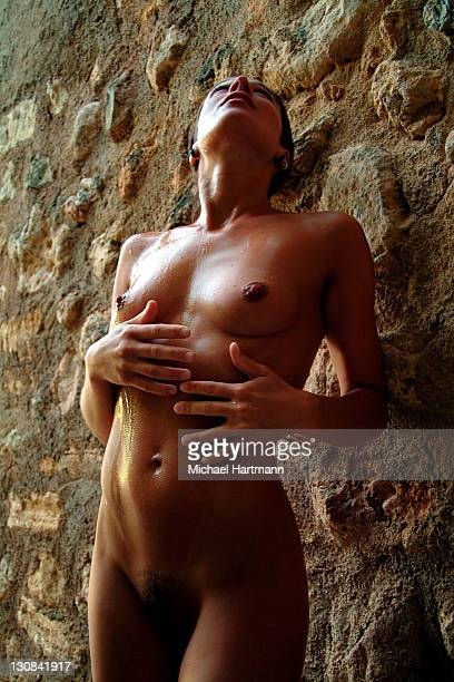 Naked young woman at a natural stone wall refreshing her skin with water, Majorca, Spain