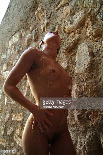 naked young woman at a natural stone wall refreshing her skin with water, majorca, spain - frau unter dusche stock-fotos und bilder