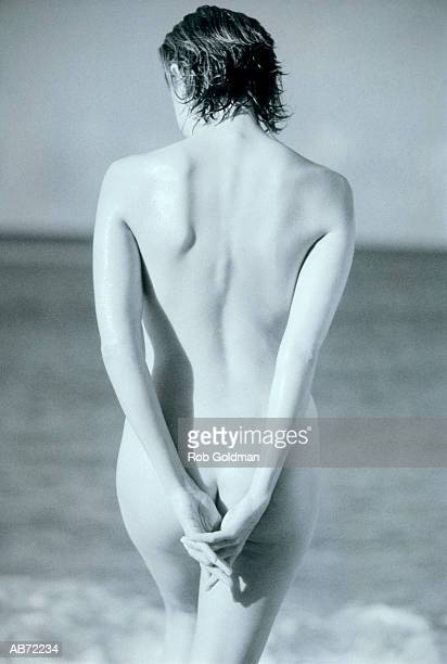 Naked young woman at beach, rear view (B&W)