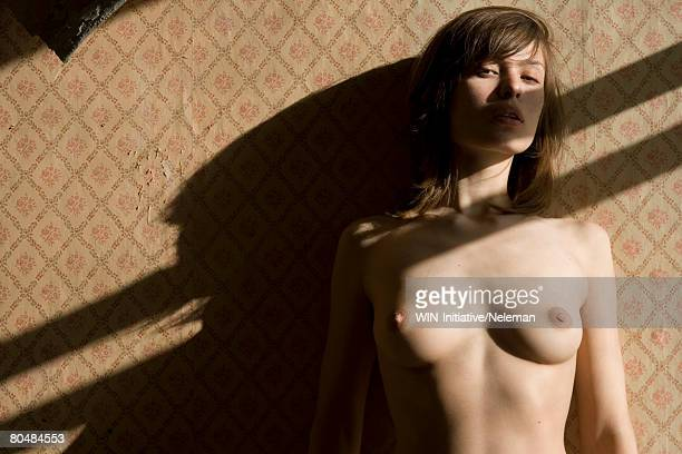 Naked young woman by wall, Portrait